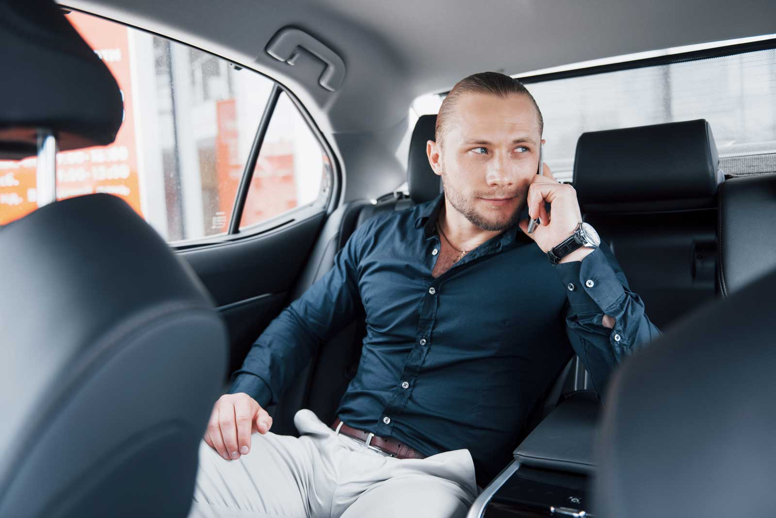 chauffeur car business man on phone in back of car